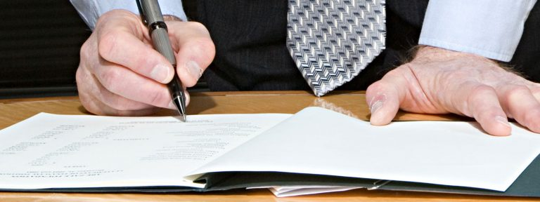 older man signing document